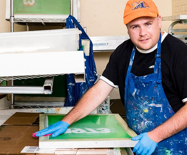 a young man working in a silk screen shop