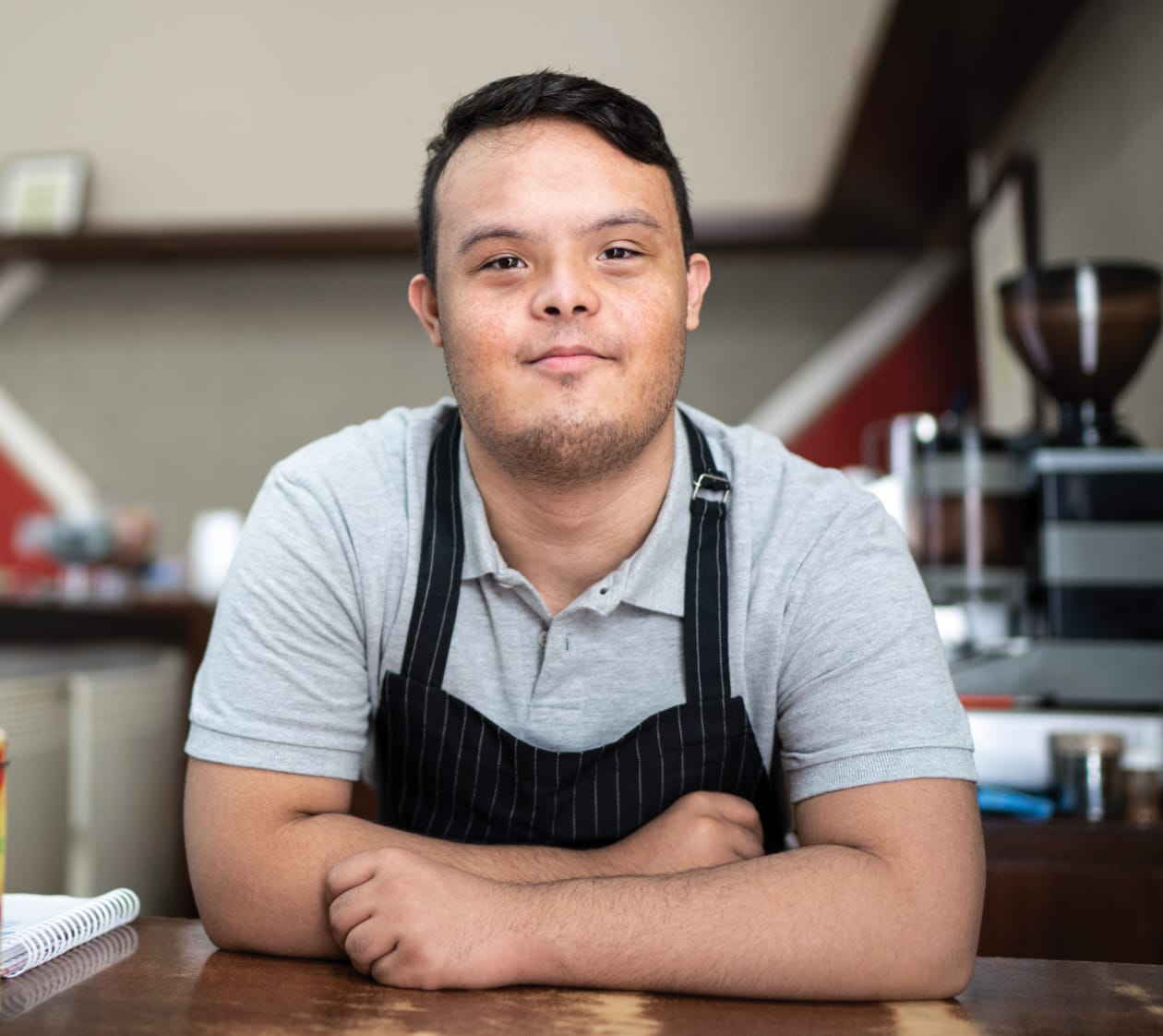 portrait of a softly smiling man wearing an apron at a coffee shop