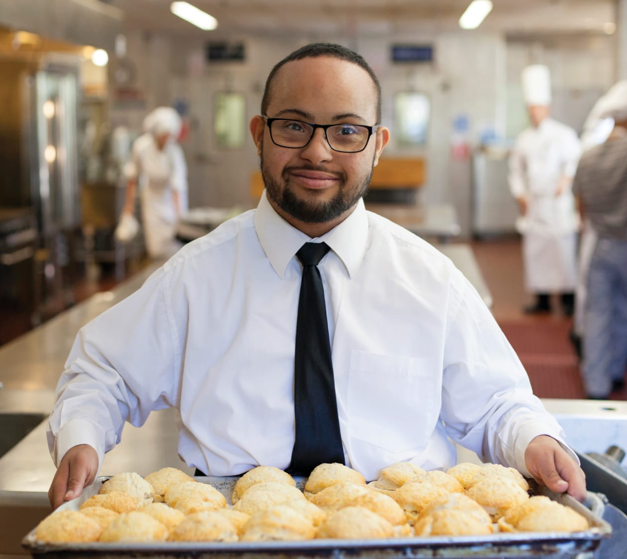 portrait of a smiling man in a tie holding a tray of pastries